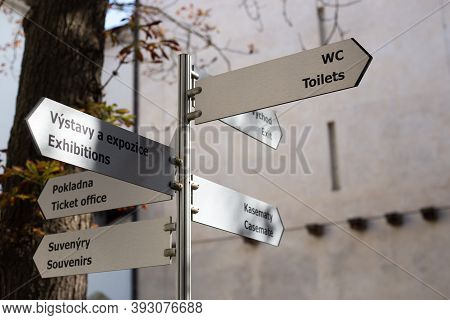 Brno, 09.10.2020 - Crossroad Signpost Saying Wc, Exit, Ticket Office And Other, Spielberg Castle Gui