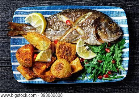Roasted Dorado Fish With Baked Potato Coated In Breadcrumbs Served On A Plate With A Lemon Wedge And