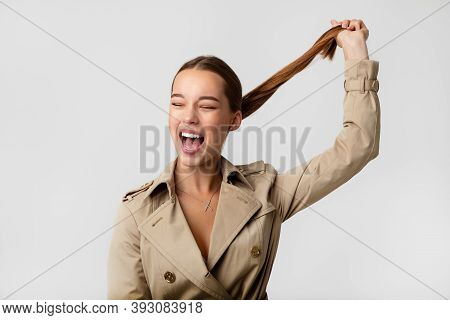 Photo Of A Beautiful Young Woman Girl In A Trench Coat. Pulls His Tail Up And Screams. Pulls Himself