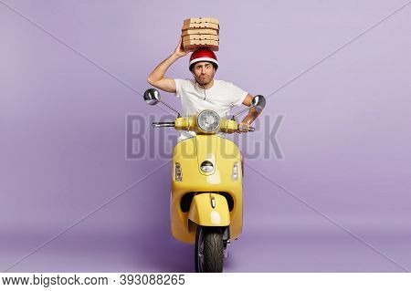 Food Delivery Service. Busy Male Courier Hurries As Conveys Cardboard Boxes With Pizza, Tries Bring