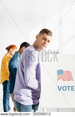 Man Looking At Camera Near Polling Booth With American Flag And Vote Inscription, And Multicultural