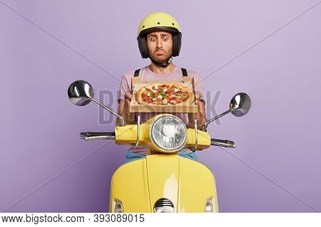 Photo Of Pizza Delivery Man Being Hungry, Looks With Temptation And Dissatisfaction At Tasty Fast Fo