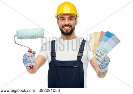 profession, construction and building - happy smiling male worker or builder in yellow helmet and overall with paint roller and color palettes over white background