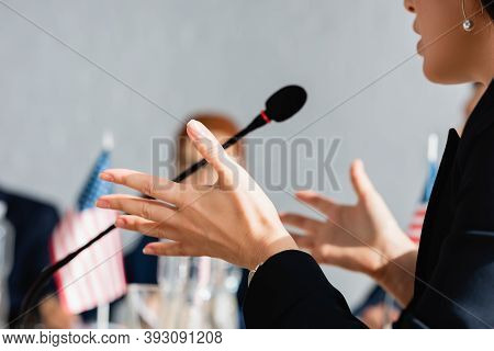 Cropped View Of Female Politician Gesturing, While Speaking In Microphone With Blurred Woman On Back