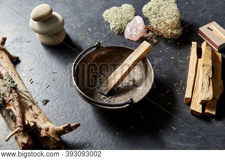 occult science and supernatural concept - palo santo stick in cup and staff for magic ritual