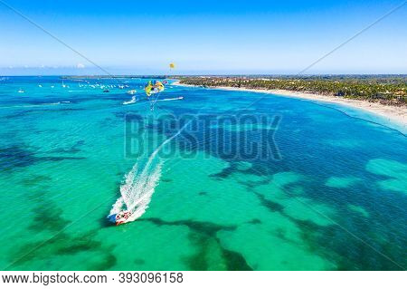 Tourists Parasailing Near Bavaro Beach, Punta Cana In Dominican Republic. Aerial View Of Tropical Re