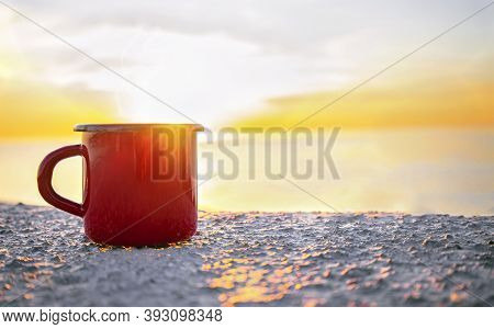 Good Morning Sunrise Concept. Red Mug With Tea Or Coffee On The Beach With Sea On Background. Sunlig