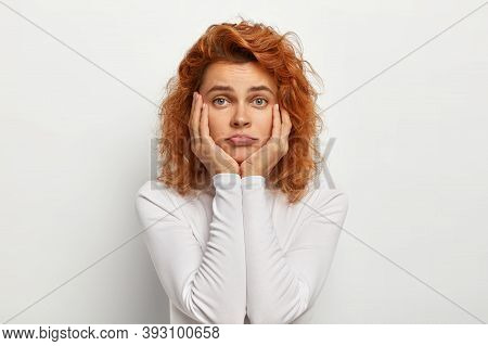 Sad Lonely Woman With Wavy Foxy Hair, Touches Cheeks, Purses Lips, Feels Bored Looks Uninterested An