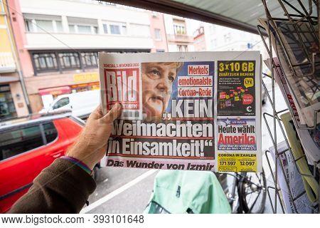 Paris, France - Nov 3, 2020: Pov Male Hand At The Newspaper German Die Bild Featuring Angela Merkel