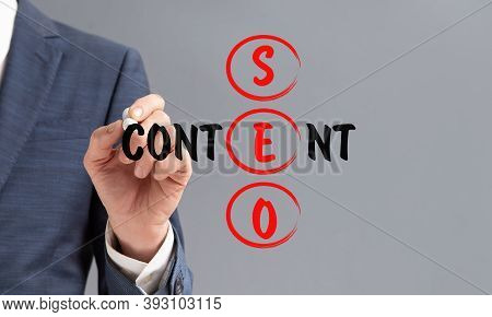 Unrecognizable Man Writing Keywords Seo And Content Standing Over Gray Background. Search Engine Opt