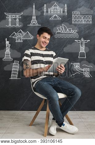 Vacation Abroad. Happy Guy Using Tablet Computer Choosing Travel Destination Online Sitting Over Bla