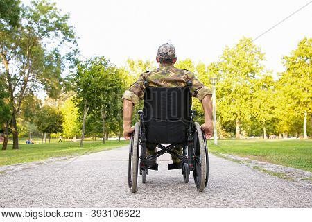 Single Disabled Retired Military Man In Wheelchair Moving Down Footpath In City Park. Back View. Vet