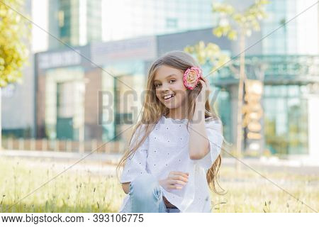 Happy Childhood. Cute Girl Holding Flower Putting It Into The Hair Smiling In The City, 8 Years Old,