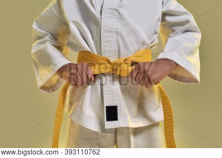 Cropped Shot Of Little Karate Girl In White Kimono Adjusting Yellow Belt While Getting Ready For Exe