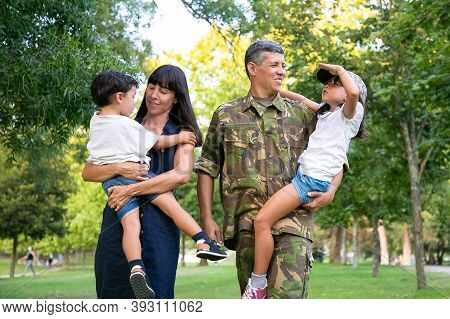 Happy Military Man Walking In Park With His Wife And Kids, Teaching Daughter To Make Army Salute Ges