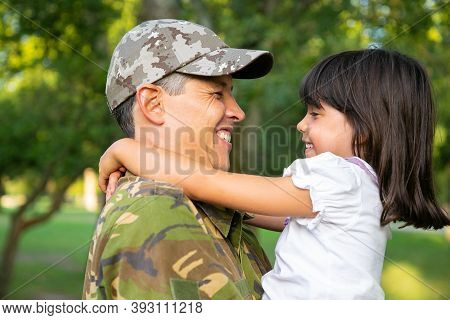 Cheerful Dad In Camouflage Uniform Holding Little Daughter In Arms, Hugging Girl Outdoors After Retu