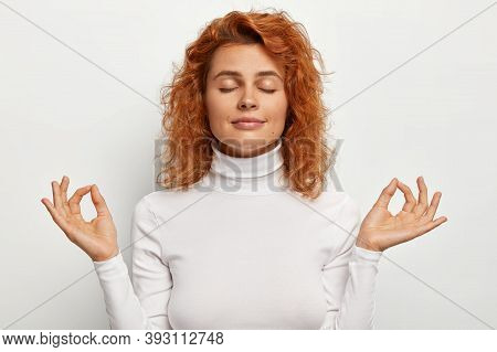 Portrait Of Calm Relaxed Beautiful Female Model Practices Yoga Meditates With Eyes Shut, Holds Hands