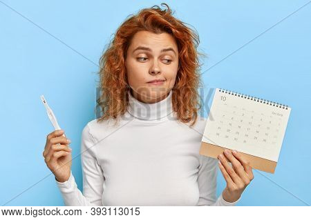 Image Of Attractive Woman Holds Pregnancy Test And Periods Calendar, Checks Menstruation Days, Finds