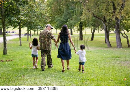 Military Man And His Family Walking In Park, Kids And Parents Holding Hands. Full Length, Back View.