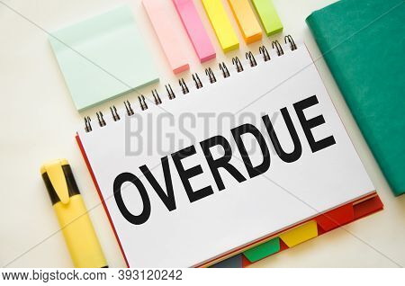 Overdue Invoices Concept. The Word Overdue Is Written On A Notepad With Markers