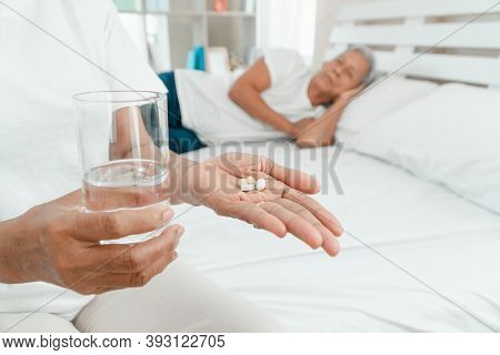 Old Elderly Woman Holding Medicine And Water On Hand On The Bed In The Bedroom And Her Husband Sleep