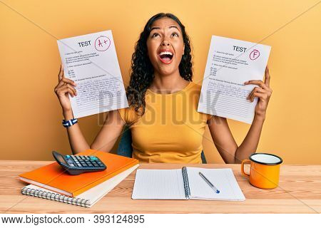 Young african american girl showing failed and passed exam angry and mad screaming frustrated and furious, shouting with anger looking up.