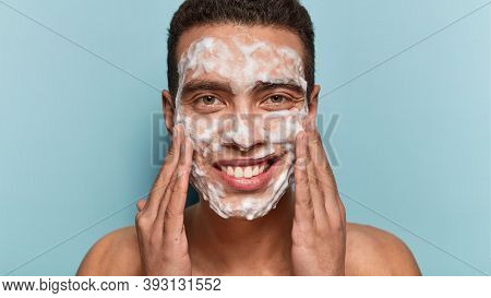 Photo Of Handsome Satisfied European Man Cleans And Washes Face With Soap, Enjoys Purity Of Skin, Sm