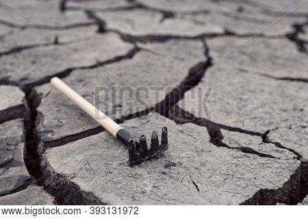Rake On The Cracked Ground, Teeth Upside Down. The Concept Of Getting On The Same Rake, Environmenta