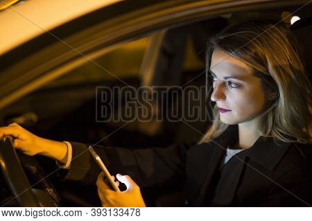 Pretty Young Woman Using Her Smart Phone While Driving Her Car At Night
