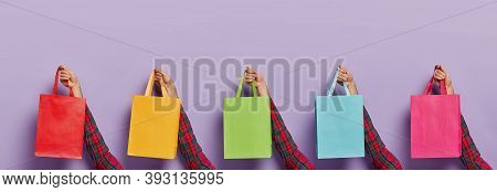 Image Of Mans Hands With Various Colorful Shopping Bags Isolated On Purple Background. Black Friday.