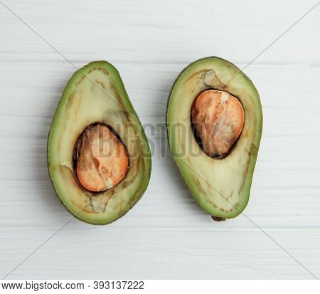 Ugly Rotten Spoiled Avocado Fruit On White Wooden Background. Ugly Food Concept