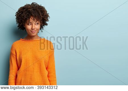 Image Of Mixed Race Woman With Cunning Sly Expression, Looks Curliously Aside, Has Intention To Impl