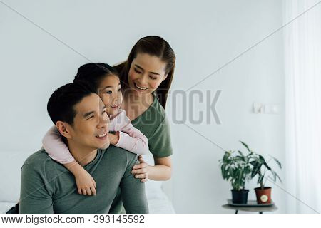 Asian Mother And Father Looking Away With Young Daughter Indoors At Home. Family Bonding And Happine