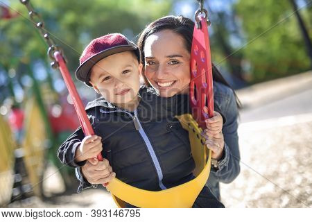 Happy Mother Pushing Son On Swing In A Park