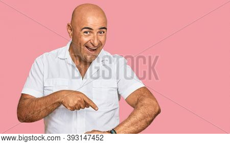 Mature middle east man with mustache wearing casual white shirt in hurry pointing to watch time, impatience, upset and angry for deadline delay