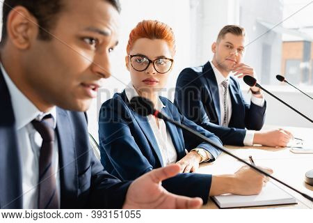 Redhead Female Politician Looking At Indian Colleague Speaking In Microphone During Political Party