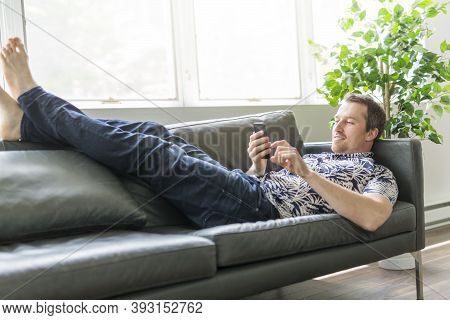 Man Using Cell Phone While Laying On Couch