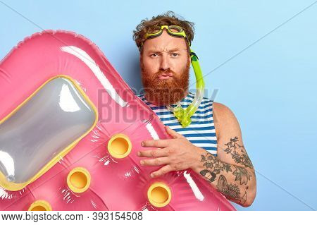 Displeased Bearded Guy Poses With Pink Air Mattress, Wears Swimming Goggles And Diving Mask, Explore