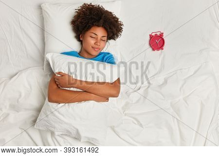 Indoor Shot Of Satisfied Dark Skinned Woman Has Rest In Bed, Sleeps Well, Focuse On Red Alarm Clock,