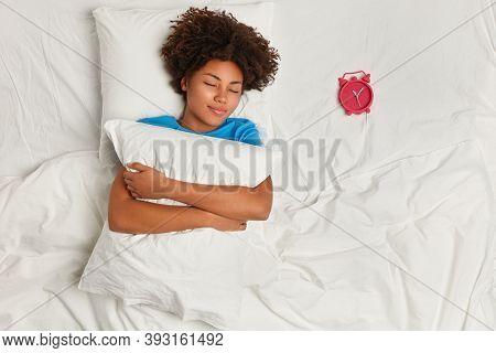 Indoor Shot Of Satisfied Dark Skinned Woman Has Rest In Bed, Sleeps Well, Focuse On Red Alarm Clock,