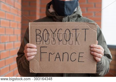 A Man In A Protective Mask Holds A Cardboard Poster With The Inscription Boycott Of France