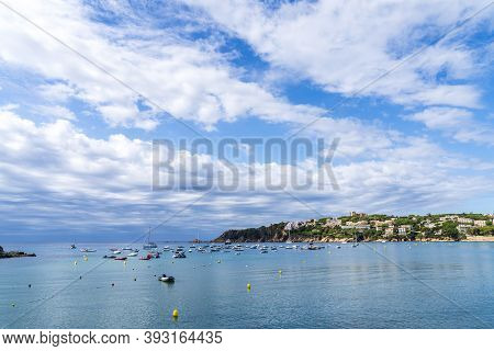 Sant Pol Beach With Boats In The Sea In A Day With Some White Clouds.