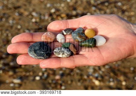 Close-up Of Female Hands Holding Colorful Beach Rocks With Blurred Beach Background.