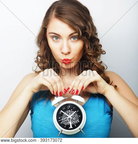 Young curly woman with alarmclock