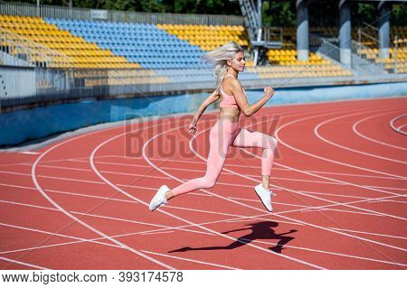 Athletic Lady Run On Stadium Running Track. Female Athlete Ready For Sprint Sport Workout. Trainer O