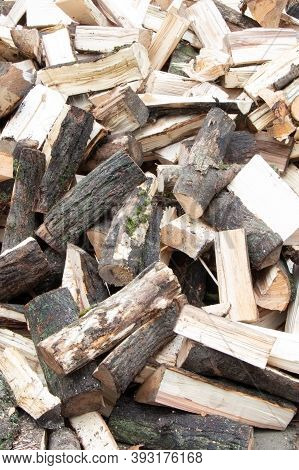 Heap Of Chopped Firewood Background. Pile Of Split Firewood. Stack Of Fuel Wood. Vertical View