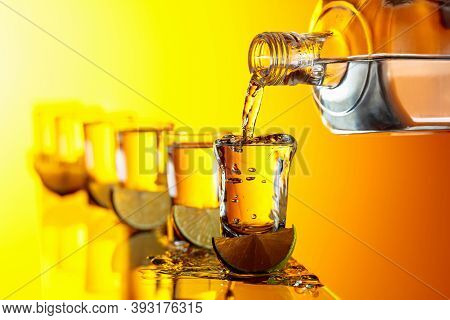 Tequila With Lime Slices On A Yellow Background. Pouring A Strong Alcoholic Drink Into Small Glasses