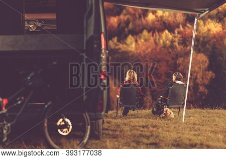 Scenic Fall Foliage Rv Camper Camping. Caucasian Couple Seating Next To Their Motorhome And Enjoying