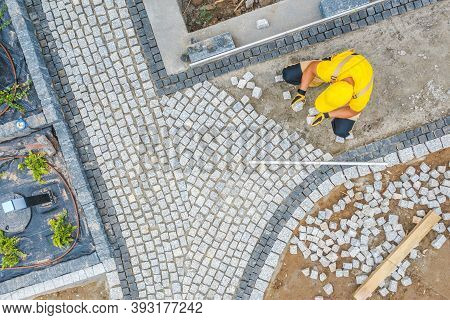 Caucasian Construction Worker In His 40s Paving Garden Path Aerial View. Garden Architecture Theme.