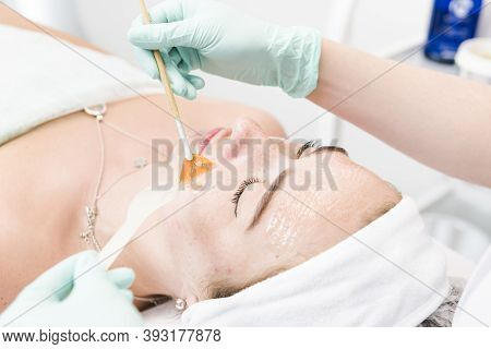 The Young Female Client Of Cosmetic Salon Having A Cleansing Facial Mask. The Procedure Of Applying